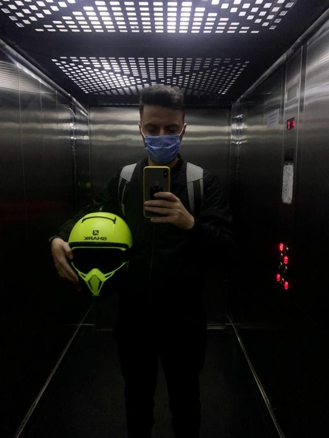 אדם במעלית עם מסיכה בגלל הקורונה